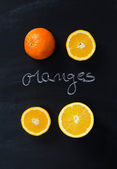 "Orange fruits and handwritten word ""oranges"" — Stock Photo"