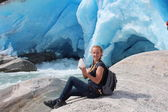 Young woman on the Nigardsbreen, sitting with piece of ice. Glacier in Norway. — Stock Photo