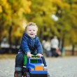 Little boy with curly hair riding a toy car on a background of a — Stock Photo #58207573