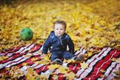 Kinky baby with blue eyes sitting on a background of autumn leav — Stock Photo