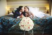 The bride and groom lying on the bed. In the foreground on the g — Stock Photo