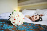 Bride lying on the bed with a wedding bouquet in a hand — Stock Photo