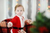 Child dressed as Santa Claus standing on a plaid chair — Foto de Stock
