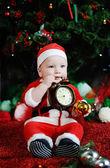 Child dressed as Santa Claus gnawing teeth clock alarm clock. — Stock Photo