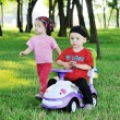 Little boy and girl on a toy car — Stock Photo #76299503
