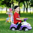 Little boy and girl on a toy car — Stock Photo #76299527