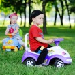 Little boy and girl on a toy car — Stock Photo #76299529