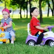 Little boy and girl on a toy car — Stock Photo #76299533