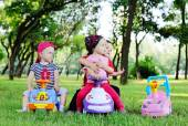Little boy and girl driving a toy car. Baby boy embraces girl — Stok fotoğraf