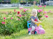 Baby girl driving pink toy car on a background of roses — Stock Photo