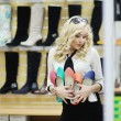 Beautiful girl chooses shoes. blonde girl measures the boots in the store — Stock Photo #77862332