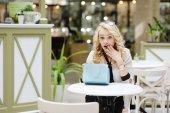 Beautiful blonde girl is considering buying — Stock Photo