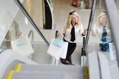 Beautiful girl with purchases on the escalator — Stock Photo