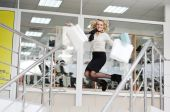 Beautiful girl jumps with purchases in hands — Stock Photo