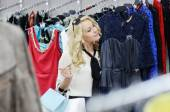 Beautiful blonde girl chooses clothes. Girl holding shopping bags. — Stock Photo