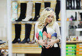 Beautiful girl chooses shoes. blonde girl measures the boots in the store — Stock Photo