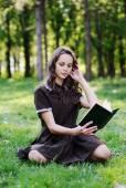 Uczennica czytając książkę siedząc na trawie. Piękna dziewczyna czytając książkę — Zdjęcie stockowe