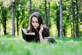 Schoolgirl reading a book sitting on the grass. Beautiful girl reading a book — Stock Photo