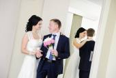 Bride and groom standing in front of a mirror — Stock Photo