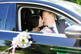 Bride and groom kissing in wedding car — Stock Photo