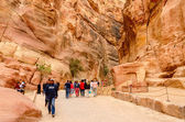 Tourists go through the gorge in Petra, Jordan — Stock Photo