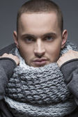 Close up portrait of young handsome man in a light grey wrap, sh — Stock Photo