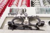 Eye test glasses on with box of many different trial lenses. Sha — Stock Photo