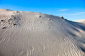 Gray sand dunes and the blue sky — Stok fotoğraf