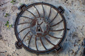 Manhole with rusty metal cover in the sandy ground — Stock Photo