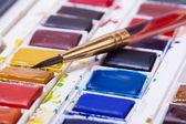 Artists watercolour paints and paint brush — Стоковое фото