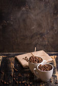 Cup with coffee beans at dark wooden background — Stock Photo