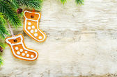Ginger biscuits and a branches of a Christmas tree — Stock Photo
