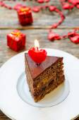 Chocolate cake with candles in the shape of a heart — Stock Photo