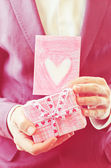 Male hand holding card and gift — ストック写真
