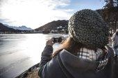 Woman takes a picture of a frozen lake — Stock Photo