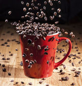 Espresso red cup with coffee beans falling — Stock Photo