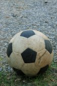 An old football on crushed gravel yard — Stock Photo