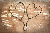 Two wire heart on wooden background — Stock Photo