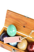 Colorful easter eggs in wood box on white background with paper  — Stock Photo