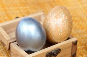 Easter eggs in small wood coffer on bamboo weave sheet backgroun — Stock Photo