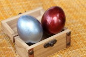 Colorful easter eggs in small coffer on bamboo weave sheet backg — Stock Photo
