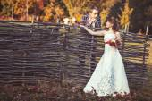 Bride and groom standing near the wicker fence — Stock Photo