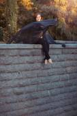 Girl dancer with black shawl sitting down on a stone wall  — Stock Photo