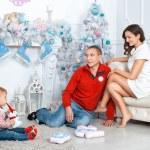 Family sitting near the Christmas tree — Stock Photo #61042991