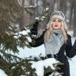 Beautiful girl in winter forest stands near a tree — Stock Photo #61043795