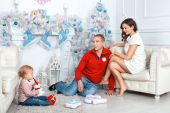Family sitting near the Christmas tree — Stockfoto