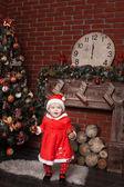 Child dressed as Santa Claus near the Christmas tree — Stock Photo