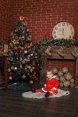 Child sits near a Christmas tree — Stock Photo