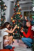 Family decorates a Christmas tree — Stock Photo