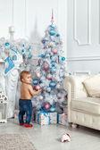 Baby girl standing near the Christmas tree — Stock Photo
